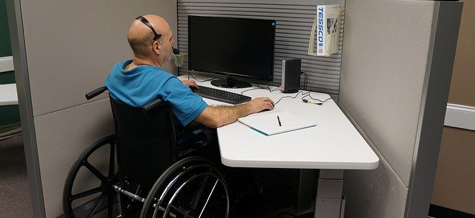 Man in wheelchair working at a desk