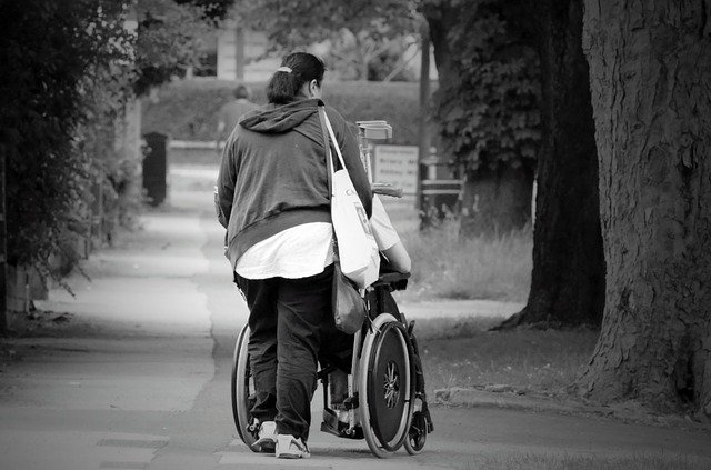 Wife is pushing her disabled husband's wheelchair