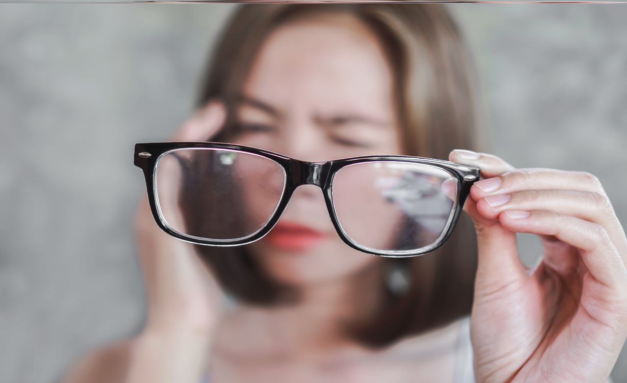 Woman has a poor vision, holding an eyeglass