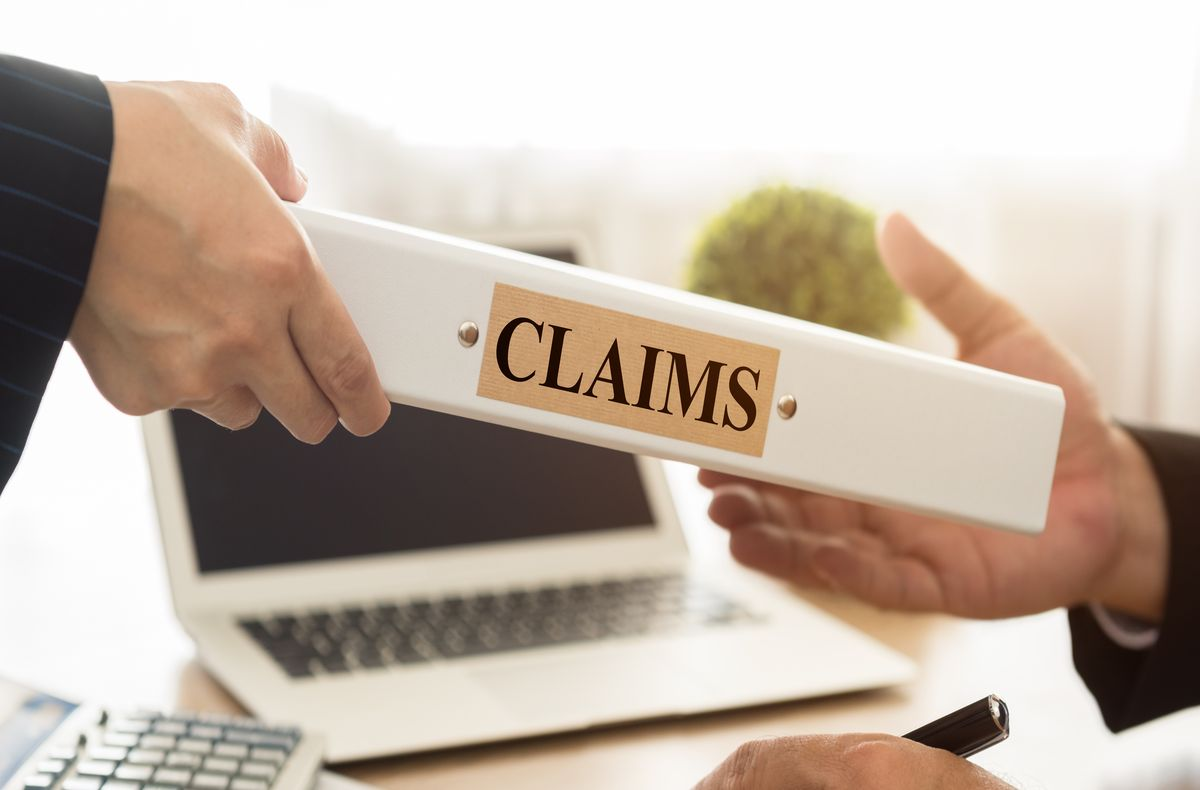 A person is delivering a claims folder to another person